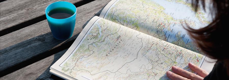 Student tittar på olika länder i en kartbok. Foto: Eva Dalin